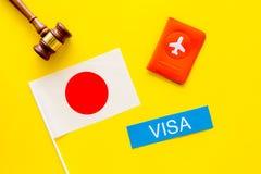 Visum aan het concept van Japan Tekstvisum dichtbij paspoortdekking en Japanse vlag, hamer op gele hoogste mening als achtergrond royalty-vrije stock foto