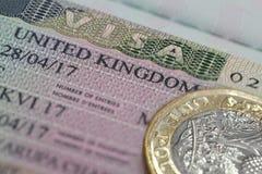 Visum Vereinigten Königreichs im Pass mit einen Pfund Münze Lizenzfreies Stockbild