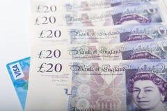 Visumkort och brittiska pund på vit bakgrund Royaltyfri Foto