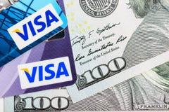 Visumskreditkarten über USA-Dollarwährungsbanknoten Stockfotografie