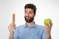 Vitórias da comida lixo em cima de uma opção saudável Imagem de Stock