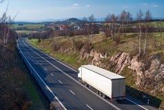 Vit åker lastbil körning längs asfaltvägbygden Fotografering för Bildbyråer