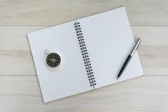 Vit öppnande tom pappers- anmärkningsbok med pennan på rätt- och navigeringkompasset på ljust - grå trätabellbakgrund med kopian arkivfoton