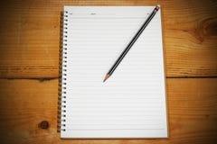 Vit anmärkningsbok för din text eller bild och en blyertspenna på träskrivbordet Arkivfoto