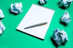vit anteckningsbok med pennan på en grön bakgrund bland pappers- bollar Begreppet av utveckling av idéer som uppfinner nya idéer  Arkivfoto