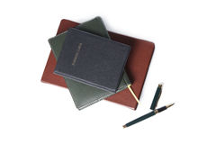 Vit anteckningsbokpappersbrunt och svart med pennan på vit bakgrund Arkivbild