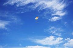 Vit-apelsinen hoppa fallskärm markisen av tandemcykeln flyger mot lodisarna royaltyfri foto