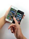 Vit Apple iPhone 5S & svart Apple iPhone 4S Royaltyfria Foton