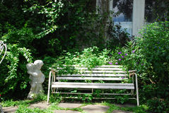 Vit bänk i gräsplanträdgård Arkivfoto