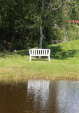 Vit bänk på sjön med vattenreflexion Arkivbilder
