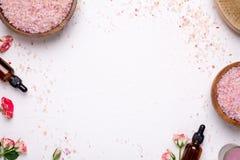 Vit bakgrund med badet saltar, massageren och naturliga oljaflaskor royaltyfri bild