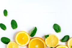 Vit bakgrund med citronen, orange skivor och mintkaramellen Begrepp med ny frukt Citron apelsin, mintkaramell ovanför sikt royaltyfri bild