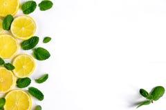 Vit bakgrund med citronen, orange skivor och mintkaramellen Begrepp med ny frukt Citron apelsin, mintkaramell ovanför sikt royaltyfria foton
