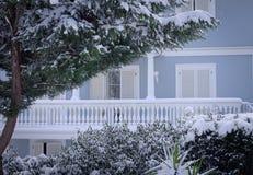 Vit balkong av ett blått hus bak snöig växter Royaltyfri Bild