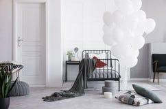 Vit ballonger bredvid enkel metallsäng med grått bädda ned och vitt och mörkt - röda kuddar i ljust scandinavian sovrum arkivbild