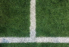 Vit bandlinje på hörnet på konstgjort grönt fotbollfält, som Copyspace för att mata in text från bästa sikt använde som mall Arkivfoton