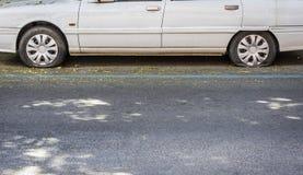 Vit bil med bristning för två gummihjul arkivbilder