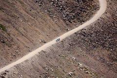 Vit bil på den avskilda vägen på det torra berget Arkivfoton