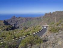 Vit bildrivig på den slingriga asfaltvägen till byn Masca med gröna kullar, skarpa bergmaxima royaltyfria bilder
