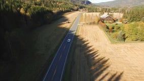 Vit bilkörning på en landsväg bland träna och fälten av Norge arkivfilmer