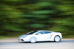 Vit bilkörning som är snabb på landsvägen Arkivfoto