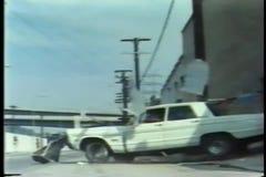 Vit bilkörning till och med garageväggen arkivfilmer