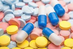 Vit-blått medicinska preventivpillerar på bakgrunden av den kulöra medicinska pi Royaltyfri Bild