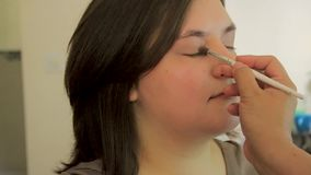 Vit blanda borste som används på ung kvinnas framsida arkivfilmer