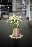 Vit blomma i en antik metalltillbringare Royaltyfri Bild