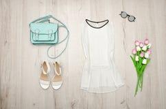 Vit blus, exponeringsglas, vita skor, handväska och en bukett av tulpan trendigt begrepp spelrum med lampa Arkivfoton