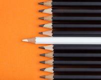 Vit blyertspenna förlagd mitt med gruppen av den svarta blyertspennan Arkivbilder