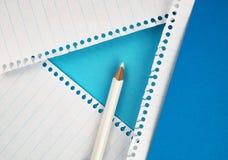 Vit blyertspenna på kulört papper Arkivbild