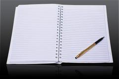 Vit bok och penna Arkivbild