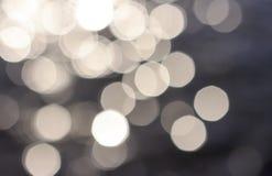 Vit bokeh på mörkt - blå bakgrundsnärbild, textur arkivfoto
