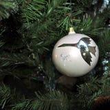 Vit boll med en bild av kranen tappningjulleksaker på trädbakgrund för nytt år arkivbilder