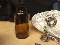 Vit bomullshandarbeteSkein av garn som strängas med krickan, blått- & bruntpärlor och brun flaska Arkivbilder