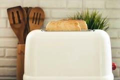Vit brödrost med rostade bröd som lagas mat i köket Royaltyfri Fotografi
