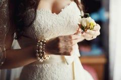 Vit bröllopboutonniere i händerna av bruden Arkivfoto