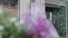Vit bröllopsklänning som dagen före hänger på en vit trähusbakgrund mot en vit vägg ceremonin arkivfilmer