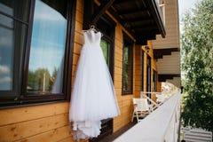 Vit bröllopsklänning som hänger på balkongen Arkivbild