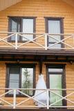 Vit bröllopsklänning som hänger på balkongen arkivfoto