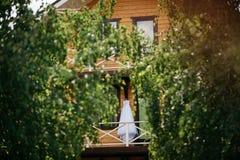 Vit bröllopsklänning som hänger på balkongen royaltyfri foto