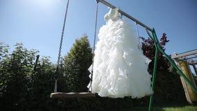 Vit bröllopsklänning som hänger på en grön gunga i trädgården lager videofilmer