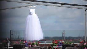 Vit bröllopsklänning som hänger på en hängare lager videofilmer
