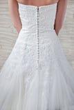 Vit bröllopsklänning som kläs för bruden, ett fragment Fotografering för Bildbyråer