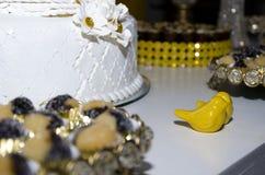 Vit bröllopstårta med gula keramiska fåglar arkivfoto