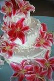 Vit bröllopstårta med många röda liljor Arkivfoton