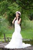 Vit brudklänning för härlig asiatisk dam som poserar i skogen Arkivbild