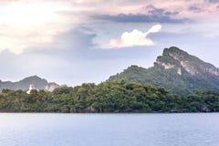 Vit Buddha på bergssidan vid havet Arkivfoton