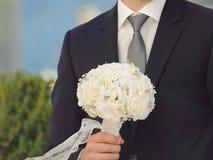 Vit bukett i brudgums hand Arkivfoton